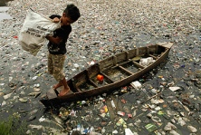 A child works on the polluted river in Jakarta. Photo: Reuters