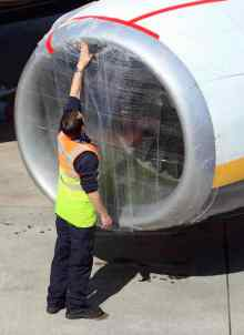 Ground staff secure a plastic cover on the engines of an aircraft at Belfast City Airport in Northern Ireland, on April 16, 2010. Thousands more flights were cancelled around the world Friday as a cloud of volcanic ash from Iceland kept airspace across northern Europe closed, inflicting a second day of travel misery on passengers. (PETER MUHLY/AFP/Getty Images)